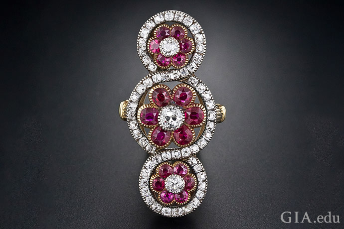 Three flowers with ruby petals glow in this Victorian-era ring. Diamonds are the hearts of the blooms, and melee diamonds surround them in a play of light.