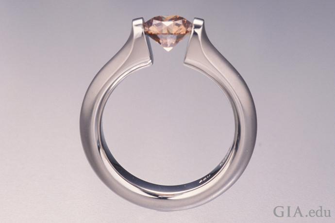 テンションセッティングは婚約指輪としてはリスクの高い選択かもしれない。この宙に浮いているに見えるダイヤモンドは、メタルセッティングの向かい合う両側における固有力により固定されている。