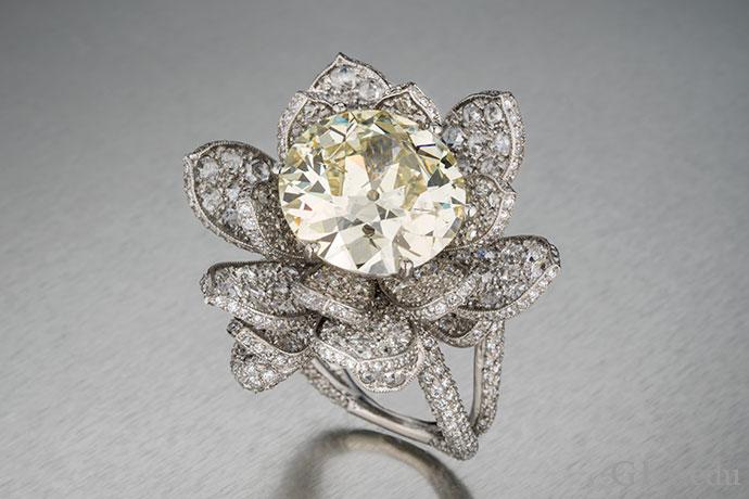 プラチナの婚約指輪にセットされ、合計5.05カラットのホワイトダイヤモンドメレーに囲まれた、11.04 ctのイエローイッシュダイヤモンド。