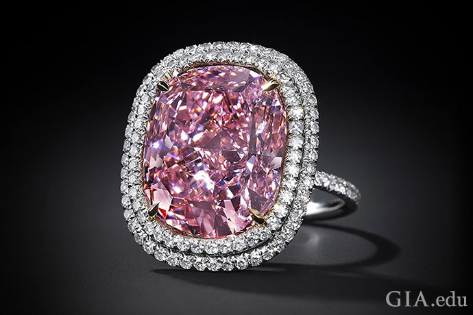 A white metal engagement ring setting and double halo of white diamonds surround a 16.08 ct Fancy Vivid pink diamond.