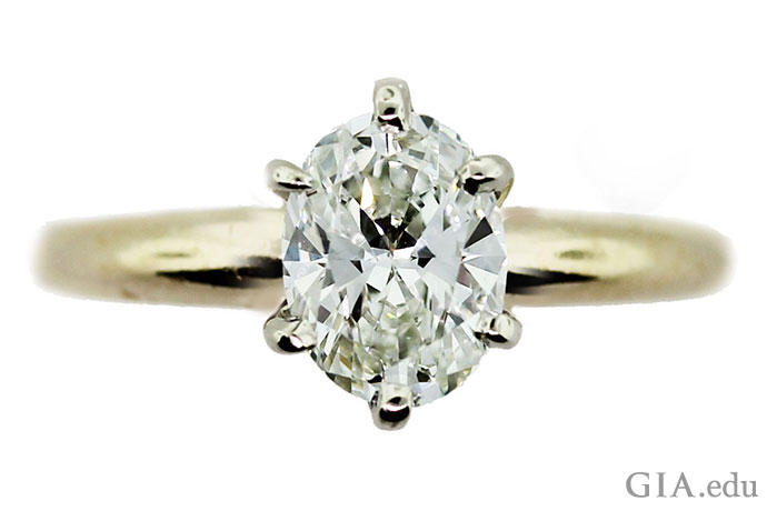 A K color diamond in a gold engagement ring setting.