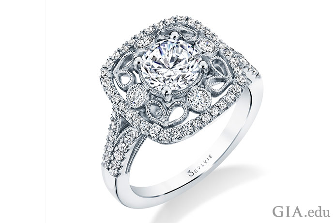 This engagement ring has a 1 ct center stone surrounded by four diamond side stones. Melee diamonds in a halo setting frame the design and continue down the shoulders of the ring.