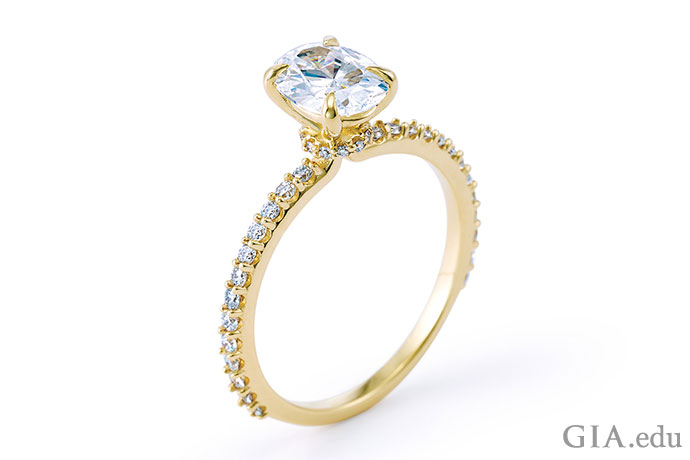 A solitaire center stone surrounded by diamond melee in a gold engagement ring setting.