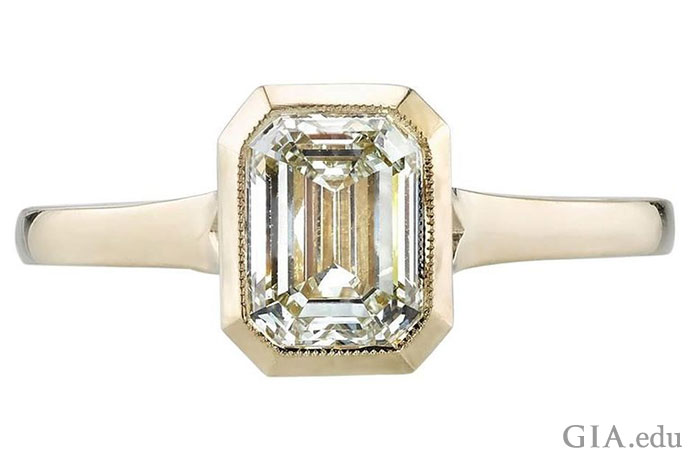 A 1.20 ct emerald cut diamond set in an 18K gold engagement ring setting.