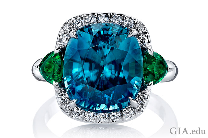 This 11.41 ct oval blue zircon with its diamond halo is like a lake that invites the viewer to peer into infinity. The tsavorite garnet side stones are leafy touches to the icy scene.