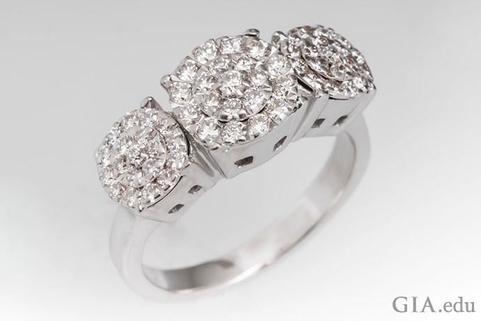采用群镶工艺的订婚戒指,创造出一种镶嵌了三颗大钻石的错觉。