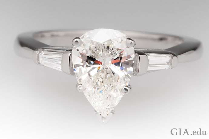A 1.4 ct pear shaped diamond engagement ring accented by two tapered baguettes.
