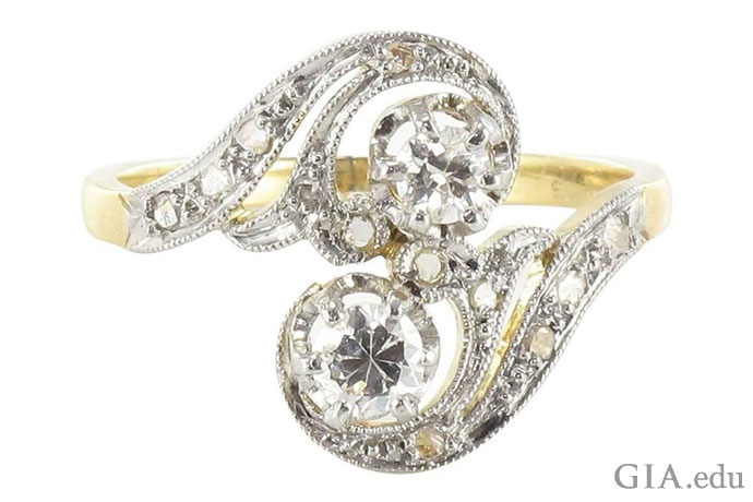 Art Nouveau style engagement ring with two diamonds trailed by curving diamond-studded lines.