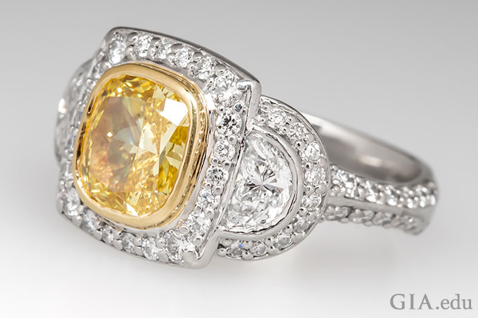 这枚订婚戒指的主石是一颗2.03克拉的艳彩黄色钻石,借助18K黄金包镶槽镶嵌于铂金之中。
