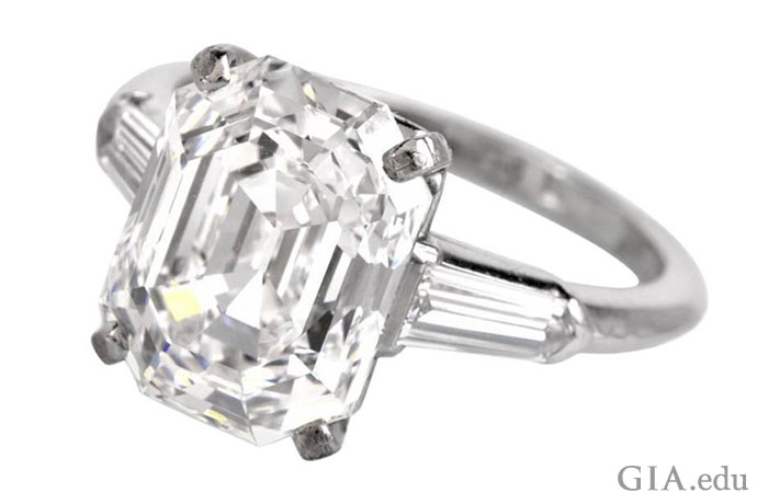 A 5.09 ct cut-cornered rectangular step cut engagement ring flanked by two tapered baguettes.