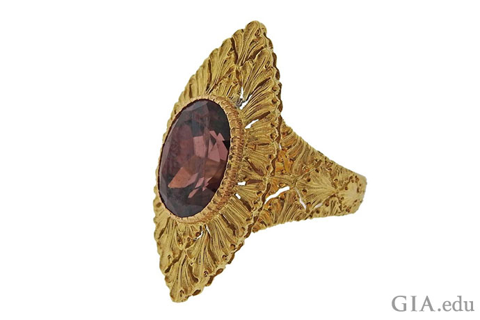A richly colored 7.23 ct zircon set in an ornate 18K gold ring looks like it belongs on the finger of European royalty.