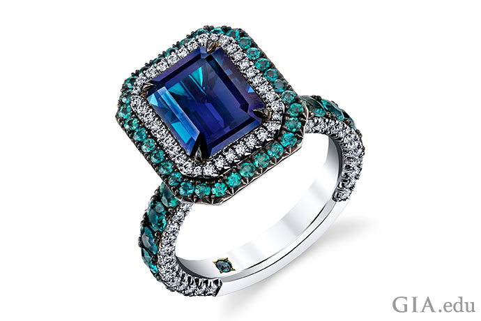 A 3.76 ct emerald cut alexandrite is framed by a halo of diamonds and another halo of alexandrites.