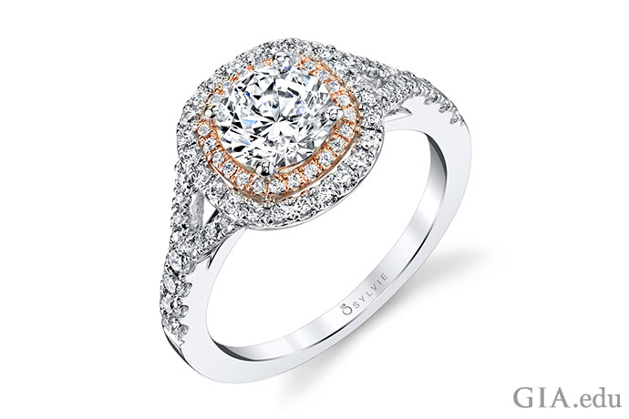 A 1.00 ct round brilliant is surrounded by halos of diamond melee set in white and rose gold.
