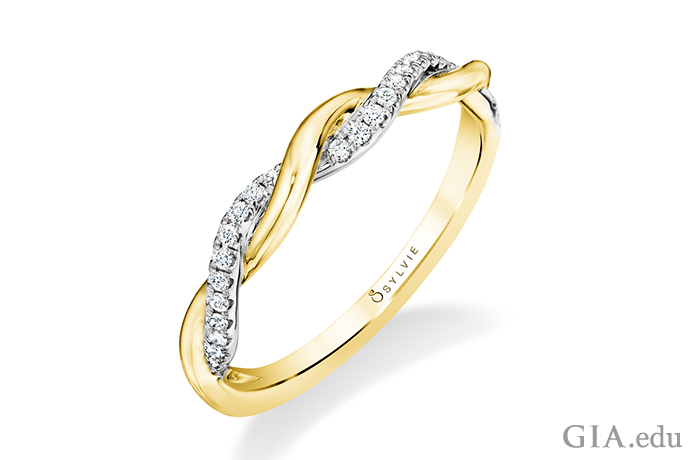 In this twisted wedding band, a row of diamonds (0.12 carats total weight) weaves its way around an unadorned yellow gold band.