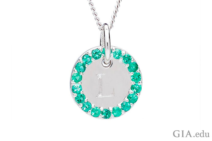 A circle of emeralds surrounds the monogram on this platinum charm.