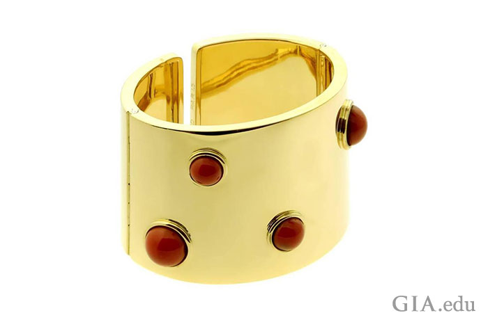 Strut your prowess by wearing a bold cuff bracelet like this contemporary creation fashioned from 18K gold and coral.