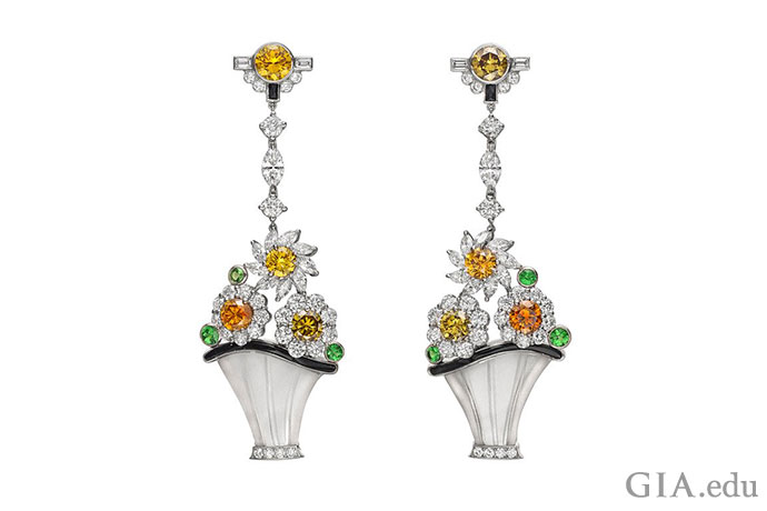 "Carved rock crystal baskets holding diamond flowers with colored diamond centers and green tsavorite garnet ""leaves"" dangle gracefully from a platinum and diamond ""rope."" These vintage pendant earrings, designed by Raymond C. Yard, feature 6.40 carats of diamonds and 0.59 carats of tsavorites with black onyx accents."