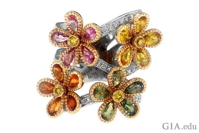 こちらは非常に繊細な自然を表しており、グリーン、オレンジ、イエロー、ピンクのサファイアで描かれる4つの回転する花がホワイトゴールドとダイヤモンドのリングを飾っている。