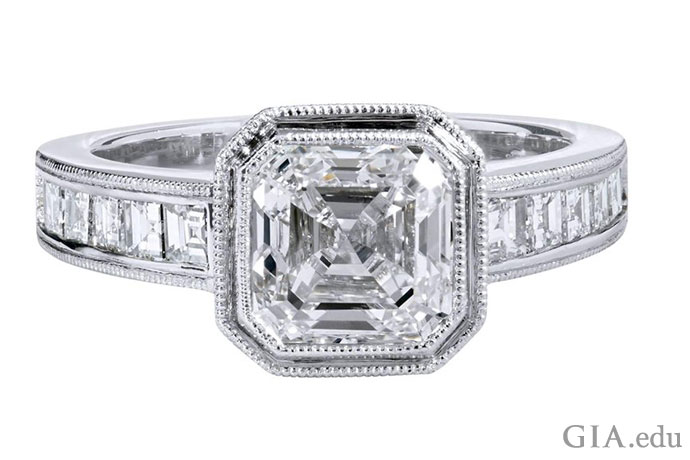 A 2.00 carat (ct) emerald cut diamond engagement ring is framed by milgrain and another 0.75 carats of diamonds in the shank.