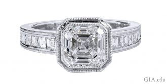 A 2.00 carat emerald cut diamond engagement ring framed by milgrain and another 0.75 carats of diamonds in the shank.