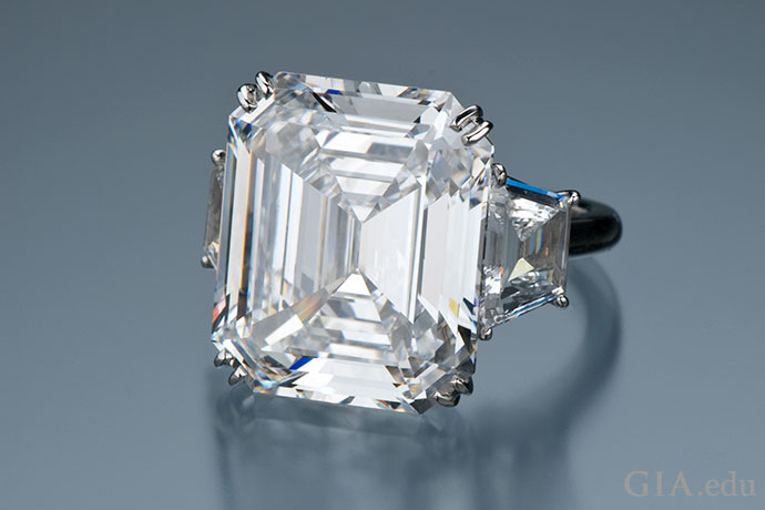 An 18.70 ct emerald cut diamond engagement ring flanked with two trapezoid-shaped diamonds.