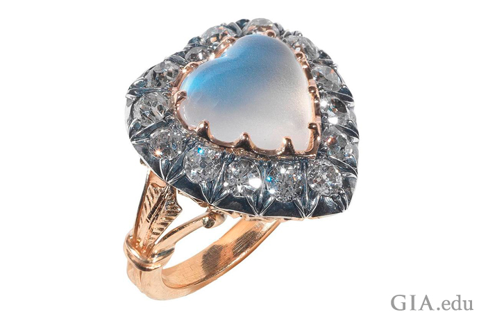 Victorian style heart shaped moonstone engagement ring surrounded with a halo if diamonds.
