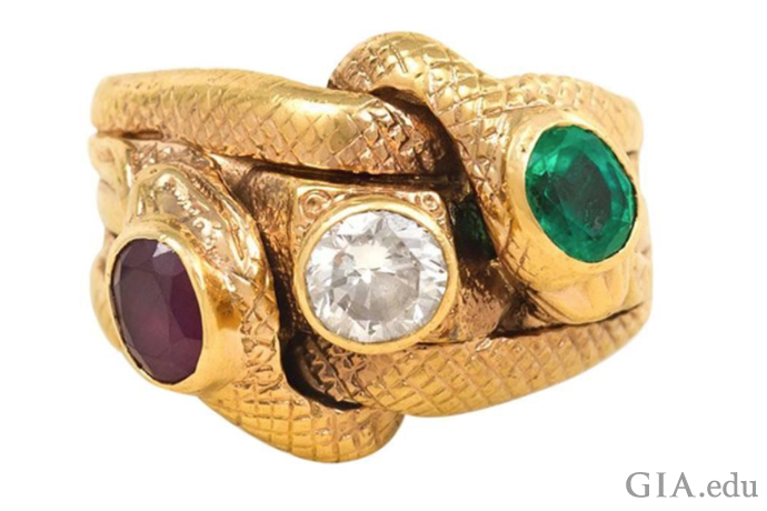 Gold snake motif engagement ring featuring two coiled serpents set with ruby, diamond and emerald.