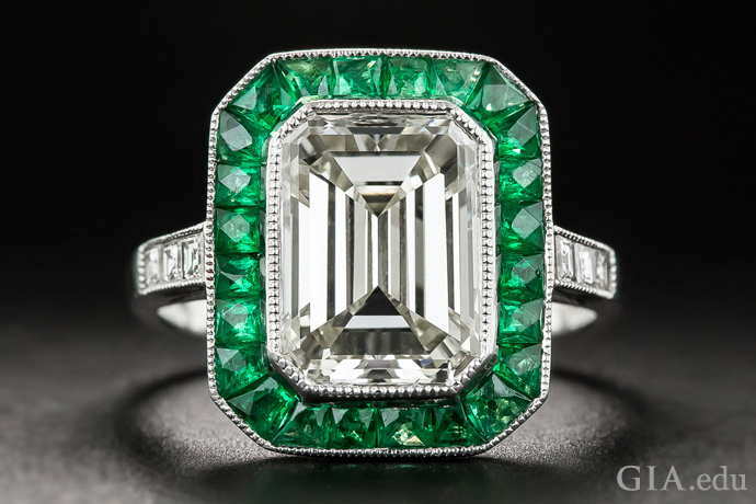 A 3.00 carat emerald cut vintage diamond engagement ring boarded by emeralds.