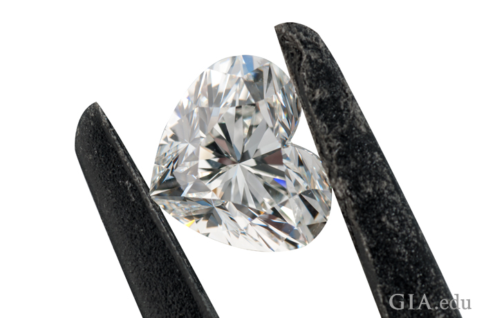 A heart shaped diamond held in a pair of jeweler's tweezers.