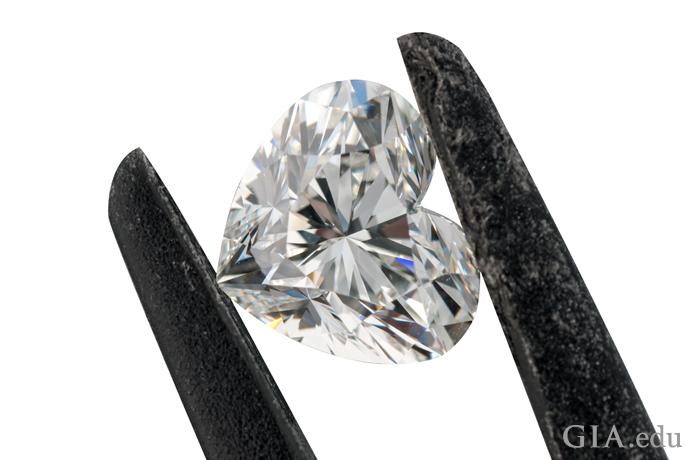ジュエラーのピンセットでつまんだハート型のダイヤモンド。