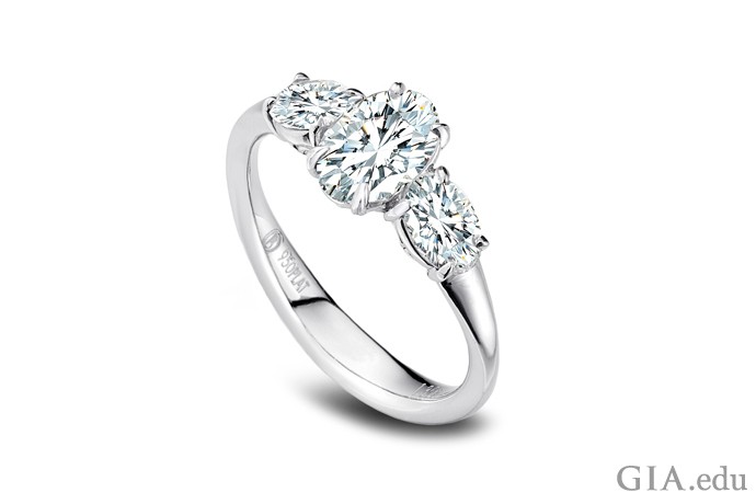 2つのサイドストーンがあしらわれたオーバルダイヤモンドの婚約指輪。