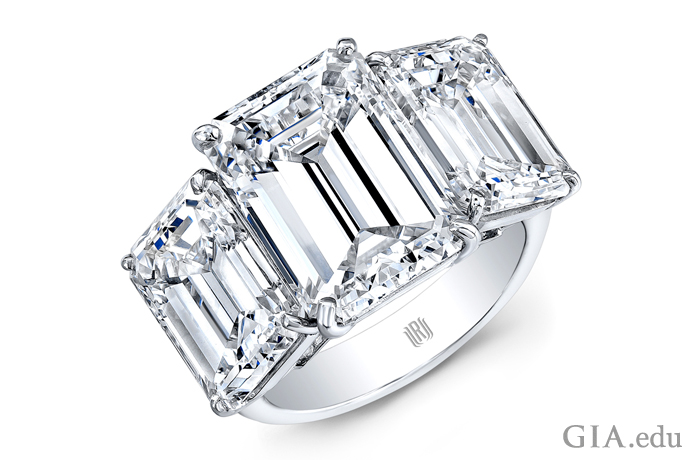 A modern diamond engagement ring featuring three emerald cut diamonds totaling 15 carats set in platinum.