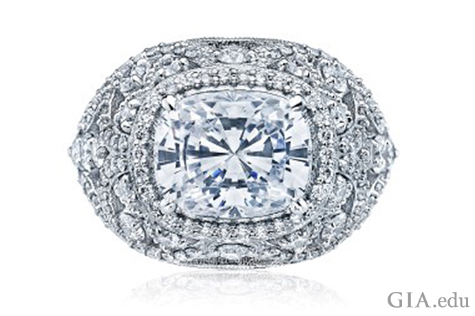 A rectangular shaped cushion cut diamond engagement ring featuring a cluster of diamonds and milgrain detail.