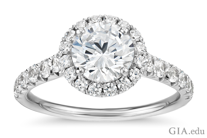 A 1.00 carat round brilliant cut diamond engagement ring accented by 0.50 carats of melee set in the halo and shank.