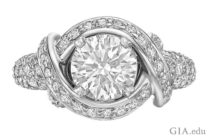 A 1.36 carat round brilliant cut diamond cradled by twisting bands of platinum studded with 0.96 carats of melee.