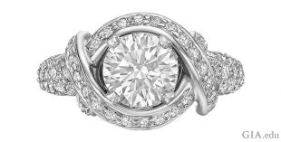 A 1.36 carat round brilliant cut diamond with twisting bands of platinum and 0.96 carats of melee.