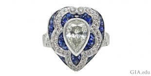 Art Deco style pear shaped engagement ring accented with radiant cut diamonds and sapphires.