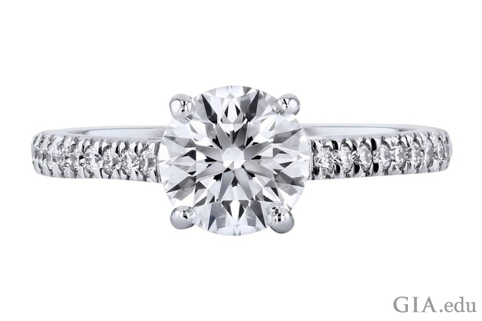 一枚镶嵌着 1.29 克拉圆形明亮式切工钻石的订婚戒指,戒圈上饰有一圈米粒钻。