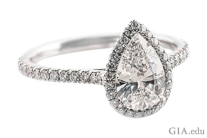 A 0.88 ct pear shaped diamond engagement ring accented with a halo of diamonds and melee in the shank.