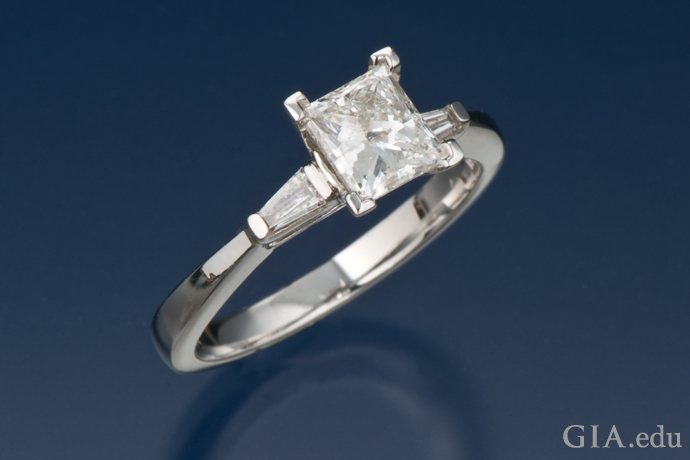 A princess cut diamond engagement ring with two tapered baguettes.