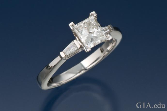 2つのテーパードバゲットがあしらわれたプリンセスカットのダイヤモンドの婚約指輪。