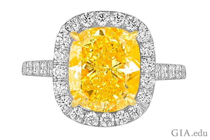 A 4.76 ct Fancy Vivid yellow diamond engagement ring surrounded by a halo of colorless diamonds.