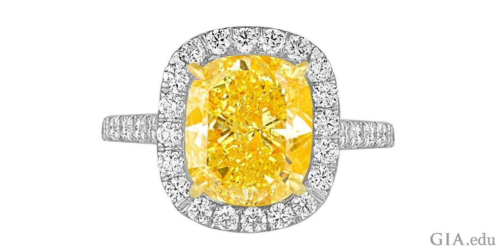 A 4.76 ct Fancy Vivid yellow diamond engagement ring with a halo of colorless diamonds.