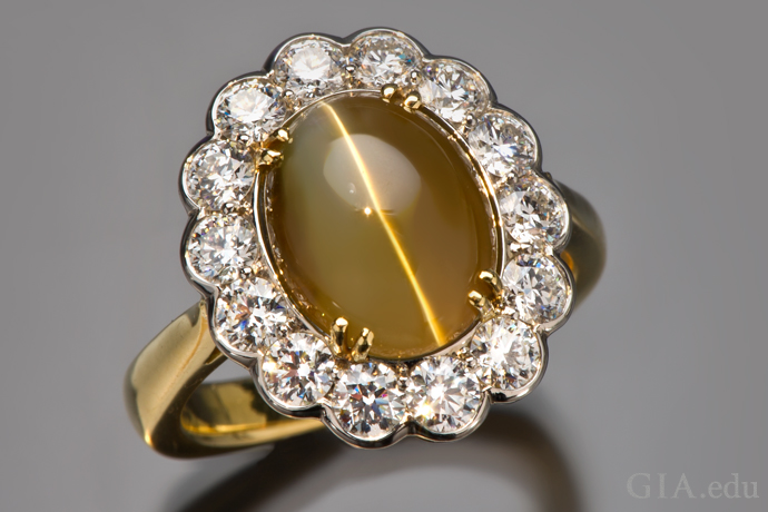 A 7.57 ct cat's-eye chrysoberyl ring surrounded by a halo of round brilliant cut diamonds.