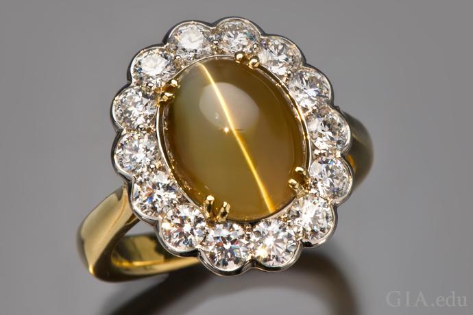 ラウンドブリリアントカットダイヤモンドのヘイローに囲まれた7.57ctのキャッツアイクリソベリルのリング。