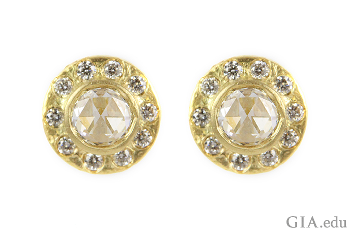 Yellow gold cradles these two rose cut diamonds, with round brilliant cut melee diamonds studded in the outer rim. The choice of metal, diamond shape and diamond cuts makes for a soothing piece.