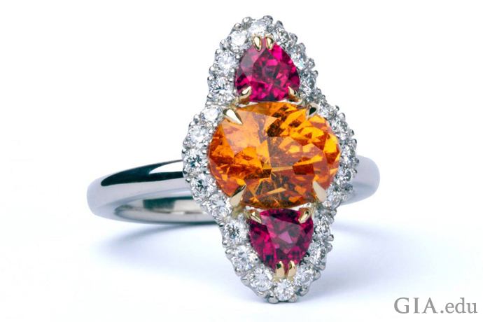 A gemstone engagement ring featuring a spessartine garnet center stone cut by John Dyer, pink tourmaline side stones and diamond melee.