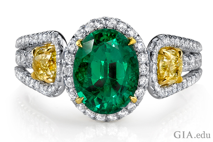 A halo of diamonds creates contrast with the emerald and helps protect this popular but fragile stone. Two yellow diamonds add more color and drama to the ring.