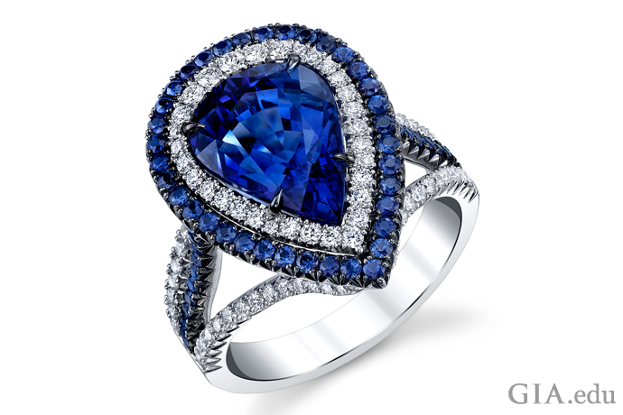 A pear shaped sapphire is surrounded by colorless diamonds and a second halo of sapphires.