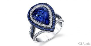 A pear shaped sapphire surrounded by colorless diamonds and a second halo of sapphires.
